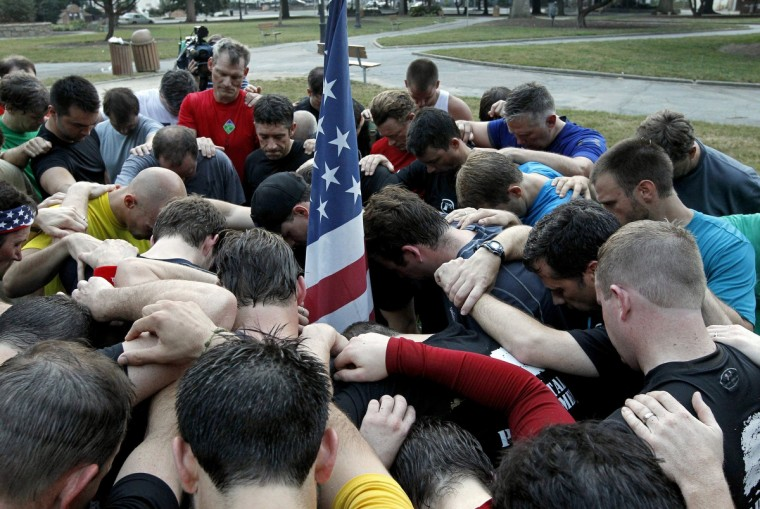 A group of about 60 men organized by the F3 fitness fellowship gather to say a prayer for the victims of the 9/11 attacks after their run in downtown Raleigh, North Carolina, Wednesday, September 11, 2013 to commemorate the 12th anniversary of the runs rescue workers made at the World Trade Centers in New York City following the terrorist attacks on Sept. 11, 2001. (Chris Seward/Raleigh News & Observer/MCT)