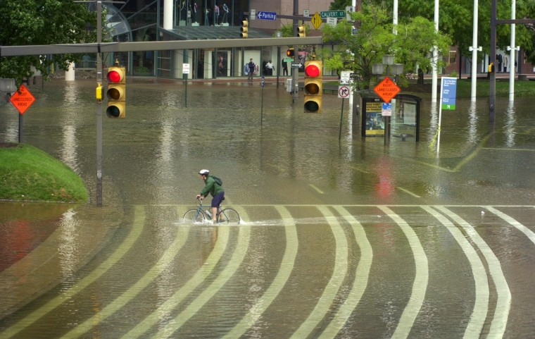 The morning after Hurricane Isabel hit, the Inner Harbor looked more like Venice, with Pratt Street closed to vehicular traffic due to flooding. An unidentified cyclist wades through water at Inner Harbor crosswalk south of Pratt Street by The Gallery. (Amy Davis/Baltimore Sun)