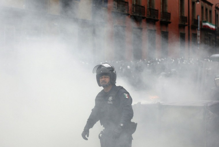A police officer stands amid smoke during protests near the Zocalo in Mexico City. (Tomas Bravo / Reuters)