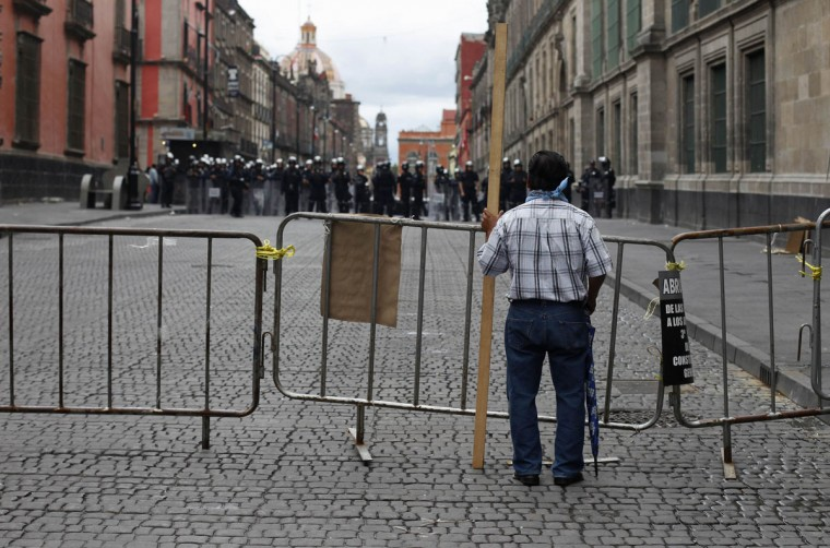A lone protester stands behind a barricade while holding onto a piece of wood near the Zocalo in Mexico City. (Tomas Bravo / Reuters)