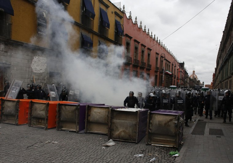 Riot policemen stand behind overturned porta potties during protests in Mexico City. (Tomas Bravo / Reuters)