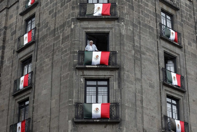 A man looks from his decorated balcony as police disperse protesters in downtown Mexico City. (Tomas Bravo / Reuters)