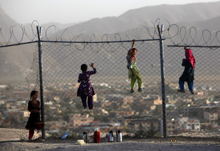 Afghan children climb onto a fence while playing as they sell tea in Kabul. A tea vendor earns $1 on average a day. (Mohammad Ismail/Reuters)