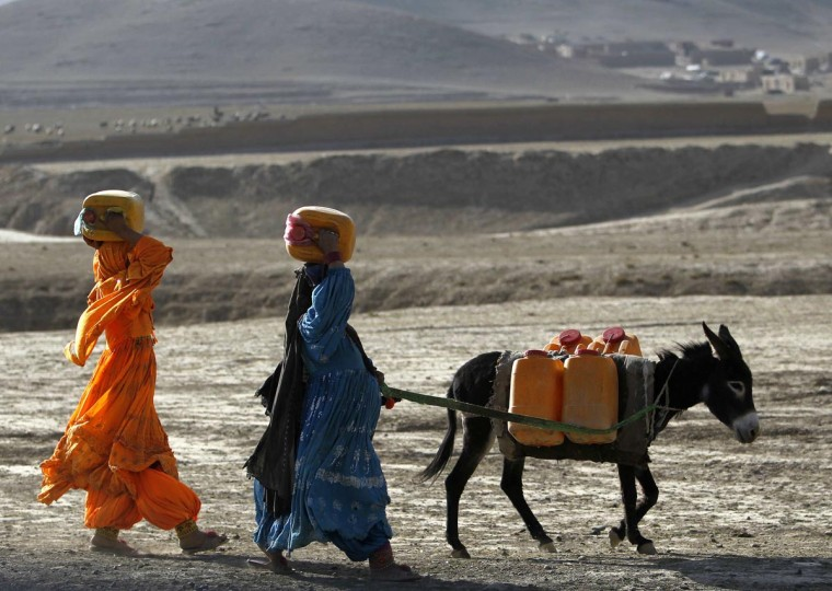 Afghan kochi nomad women carry water containers on their heads as they walk with a donkey outside of Maidan Shar, the capital of Wardak province, September 8, 2013. (Omar Sobhani/Reuters)
