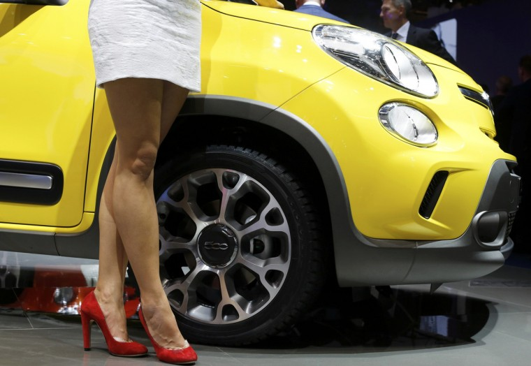 A model poses next to Fiat 500 L Trekking car during a media preview day at the Frankfurt Motor Show (IAA) September 10, 2013. (Wolfgang Rattay/Reuters photo)