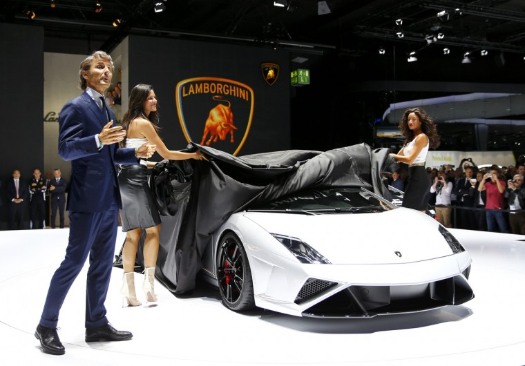 Stephan Winkelmann, President and CEO of Lamborghini speaks as models uncover a Lamborghini Gallardo LP570-4 Squadra Corse during a media preview day at the Frankfurt Motor Show (IAA). (Kai Pfaffenbach/Reuters photo)