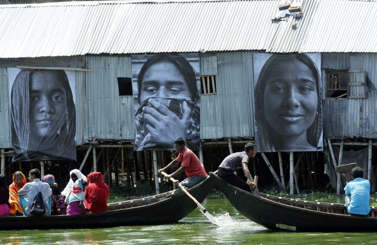"""Boats carrying slum dwellers pass photographs of garment workers taken by students of the Counter Foto photography department, by the waterfront of Korail slum at Gulshan area in Dhaka, Bangladesh on September 13, 2013. The photographs are a celebration of hardworking Bengali women, in support of their struggle for socioeconomic justice, and are part of the """"Dignity in Industry"""" project by French artist J.R. and Inside Out Project, organizers said. (Andrew Biraj/Reuters)"""