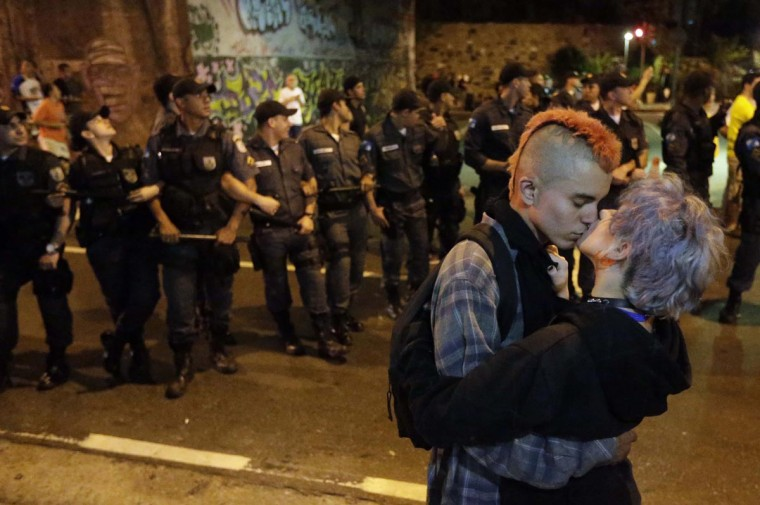 A couple, who are anti-government demonstrators, kisses next to military police officers during a protest near Guanabara Palace in Rio de Janeiro September 7, 2013. Police used teargas to contain street protests on Saturday in several Brazilian cities, stopping demonstrators from disrupting Independence Day military parades and an international soccer game between Brazil and Australia. (Ricardo Moraes/Reuters)