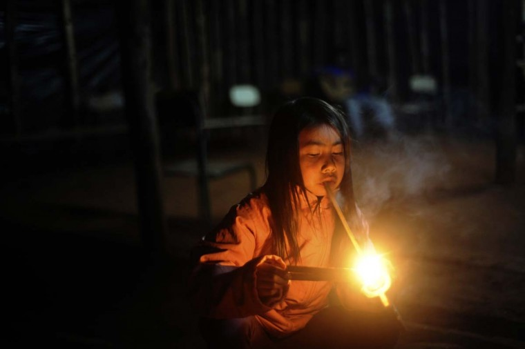 A Guarani Ava Indian child lights a ceremonial pipe called a Petygua which wards off bad spirits, during a ritual as they prepare to take back their ancestral plot of land they call Tekoha Yvoh'y, in Guaira, Parana state, near the southern border with Paraguay, July 31, 2013. The Guarani tribe is immersed in a bloody conflict with farmers over possession of their ancestral land that has characteristics of a territorial war, in spite of Brazil's indigenous policy being considered one of the most progressive in the world. The conflict highlights the risks being run by an agricultural superpower whose leftist government is trying to sort out centuries of ethnic disputes over ownership of the land from which much of the nation's wealth sprouts. (Lunae Parracho/Reuters)