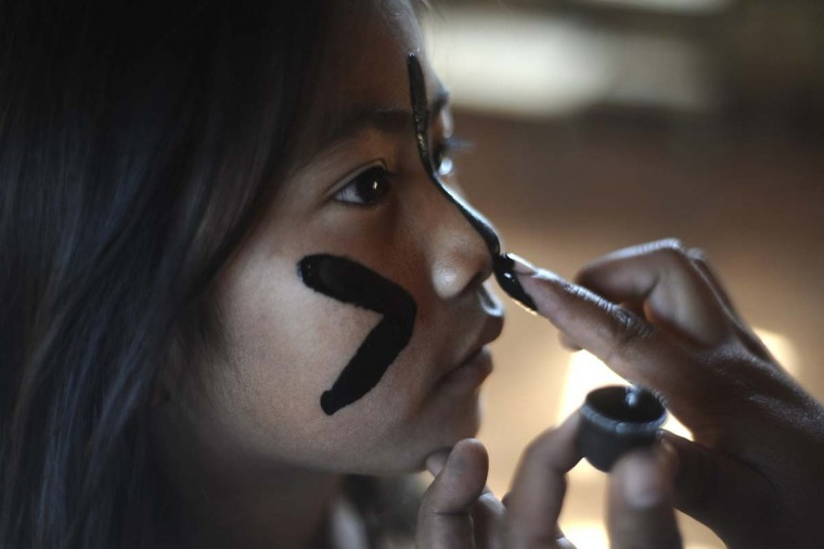 A Guarani Ava Indian girl has her face painted as they live on the edge of their ancestral land they call Tekoha Yvoh'y, while awaiting a court's decision on the eviction of farmers occupying the land, in Guaira, Parana state, near the border with Paraguay, August 2, 2013. The Guarani tribe is immersed in a bloody conflict with farmers over possession of their ancestral land that has characteristics of a territorial war, in spite of Brazil's indigenous policy being considered one of the most progressive in the world. The conflict highlights the risks being run by an agricultural superpower whose leftist government is trying to sort out centuries of ethnic disputes over ownership of the land from which much of the nation's wealth sprouts. (Lunae Parracho/Reuters)