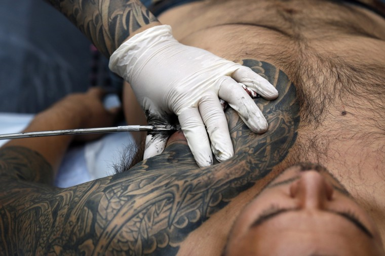 A man is tattooed by tattoo artist Chosu Horikazu (L) during the ninth London International Tattoo Convention in London September 27, 2013. (Stefan Wermuth/Reuters photo)