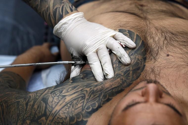 A man is tattooed by tattoo artist Chosu Horikazu (L) during the ninth London International Tattoo Convention in London September 27, 2013. (Stefan Wermuth/Reuters photo)