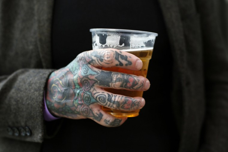 A tattooed man holds a beer during the ninth London International Tattoo Convention in London September 27, 2013. (Stefan Wermuth/Reuters photo)
