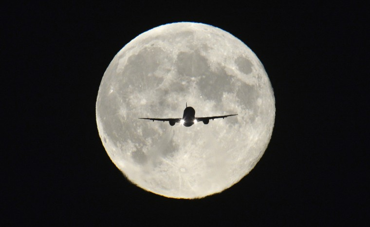 """A passenger aircraft, with the full """"Harvest Moon"""" seen behind, makes its final approach to landing at Heathrow Airport in west London. The Harvest Moon is a traditional name for the full moon that is closest to the autumn equinox, and at a traditional period where farmers would be harvesting crops. The moon's rise time and angle of path give the illusion that the Harvest Moon is both closer, larger and brighter; though actually it is not. (Toby Melville/Reuters photo)"""