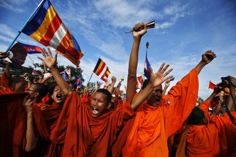Buddhist monks who are supporters of the Cambodia National Rescue Party (CNRP), react during a protest as party leader Sam Rainsy announces the result of a meeting with Cambodian Prime Minister Hun Sen, at Freedom Park in Phnom Penh September 16, 2013. Hun Sen met opposition leader Sam Rainsy for talks and officials said they had agreed to look at how future general elections are held but the long-serving premier refused to give in to demands for an independent inquiry into the July 28 poll. The protest was staged a day after police used force to scatter protesters challenging a disputed election win by Hun Sen, sparking clashes in which one man was shot dead. (Athit Perawongmetha/Reuters)