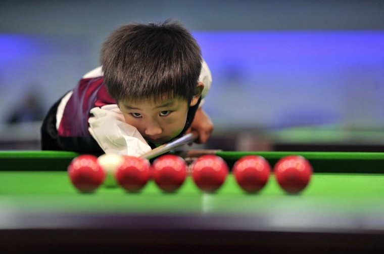 Three-year-old Wang Wuka practises before playing snooker with seven-time World Championship winner Stephen Hendry of Britain in Beijing September 22, 2013. Wuka's father Wang Yin, a snooker fan, has been teaching his son the sport for more than two years. The boy, who vows to be a top snooker player, undergoes five hours of training daily to shoot the balls with precision. Picture taken September 22, 2013. (Reuters)