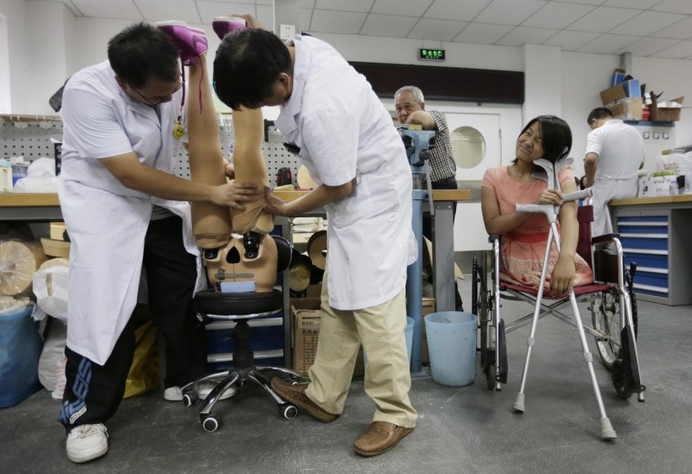 Qian Hongyan, 18, waits for her new prosthesis which are being fitted with silk stockings at China Rehabilitation Centre in Beijing, September 5, 2013. Qian, who has been moving by using a basketball after she lost her legs in a car accident at age four, got her new free prosthesis fitted for her adult body. She first received artificial limbs in 2005 and later joined a swimming club for the handicapped and became an athlete. (Jason Lee/Reuters)
