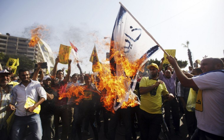 """Members of the Muslim Brotherhood and supporters of ousted Egyptian President Mohamed Mursi shout slogans against the military and interior ministry as they burn a flag reading, """"Egypt's Army Chief General Abdel Fattah al-Sisi is a traitor"""" during a protest near Rabaa al-Adawiya square, at Cairo's Nasr City district, September 13, 2013. Thousands of pro-Mursi protesters marched after Friday prayers in several areas of Cairo after authorities boosted security in sites where crowds had gathered in the past. (Amr Abdallah Dalsh/Reuters)"""