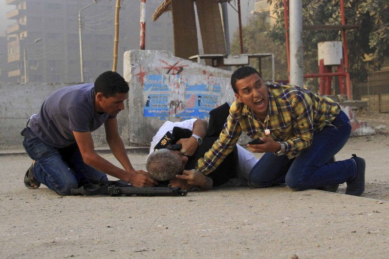 Members of the Egyptian security forces attempt to help the Police Chief General Nabil Farag (C), who was killed after unidentified militants opened fire on security forces deployed early morning, in Kerdasa, a town 14 km (9 miles), from Cairo. (Stringer/Reuters photo)