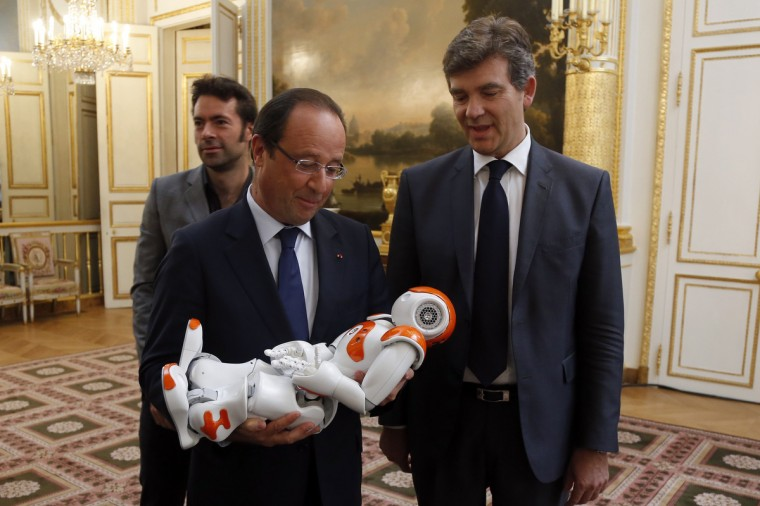 "France's President Francois Hollande holds an humanoid robot ""Nao"" from Aldebaran Robotics company as he visits an exhibition on French industrial design and technology at the Elysee Palace in Paris, . At R, French Minister for Industrial Recovery Arnaud Montebourg. (Charles Platiau/Reuters)"