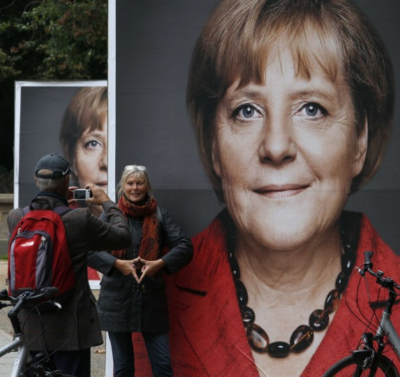 People take a picture in front of an election campaign poster showing German Chancellor and head of the Christian Democratic Union party (CDU) Angela Merkel in Berlin. German voters will take to the polls in a general election on September 22. (Fabrizio Bensch/Reuters photo)