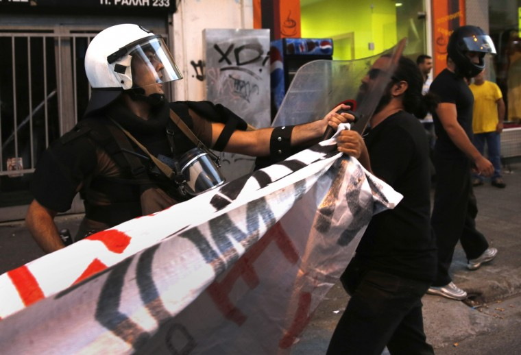 A riot policeman hits a protester with his shield during a peaceful anti-fascist rally following the killing of a 35-year-old anti-racism rapper by a man who sympathizes with the far-right Golden Dawn group in an Athens suburb.The Greek government asked judges to move against Golden Dawn, saying it had evidence the far-right party was a criminal organisation and a threat to public safety. (Yannis Behrakis/Reuters photo)