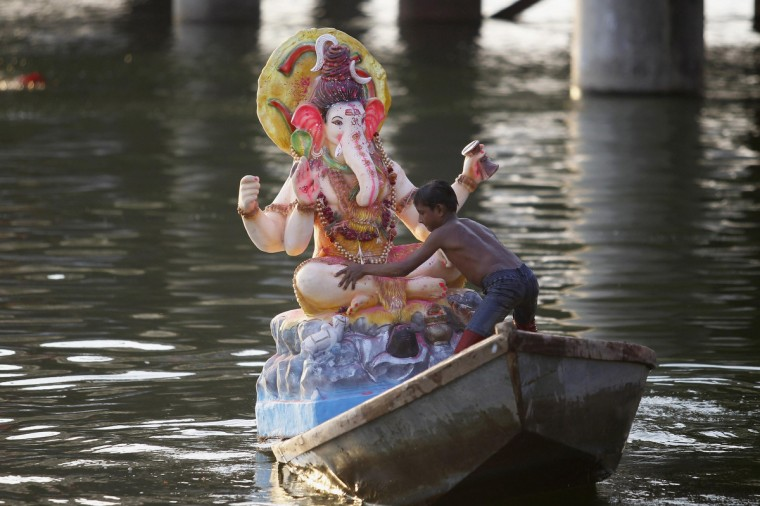 A devotee immerses an idol of the Hindu elephant god Ganesh, the deity of prosperity, in the Sabarmati river on the last day of the Ganesh Chaturthi festival in the western Indian city of Ahmedabad. During this festival, idols of Ganesh are taken through the streets in a procession accompanied by dancing and singing and later immersed in a river or the sea, symbolizing a ritual seeing-off of Ganesh's journey towards his abode, taking away with him the misfortunes of all mankind. (Amit Dave/Reuters)