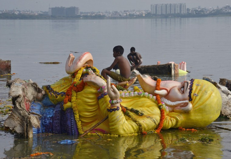 A boy sits on an idol of the Hindu elephant god Ganesh, the deity of prosperity, after it was immersed in the waters of Hussain Sagar lake to mark the end of 10-day-long Ganesh Chaturthi festival in the southern Indian city of Hyderabad. (Krishnendu Halder/Reuters photo)