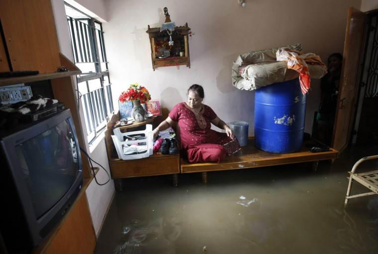 A woman sits on a bed inside her flooded room after heavy rains in the western Indian city of Ahmedabad. (Amit Dave/Reuters)