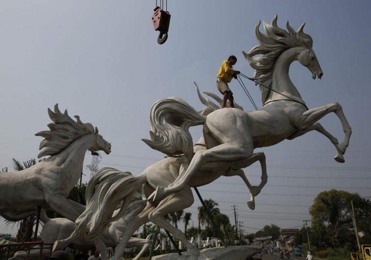 A worker tightens a rope to raise a four-meter-high (13 ft) statue of horses at a new housing complex at Parung village in Bogor, Indonesia's West Java province. (Beawiharta/Reuters photo)