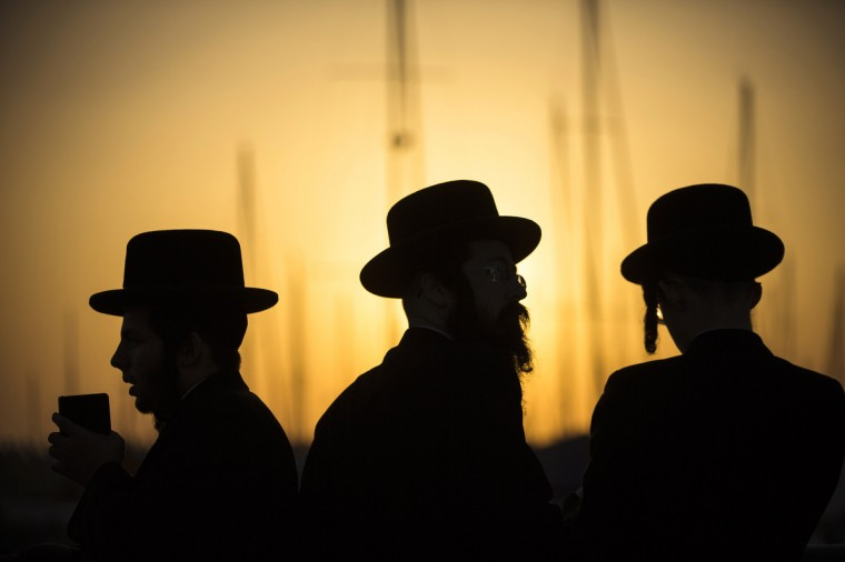 Ultra-Orthodox Jewish men are silhouetted as they pray during the Tashlich ritual near the shore of the Mediterranean Sea in the southern city of Ashdod ahead of Yom Kippur, the Jewish Day of Atonement, which starts at sundown Friday. Tashlich is a ritual of casting away sins of the past year into the water. (Amir Cohen/Reuters)