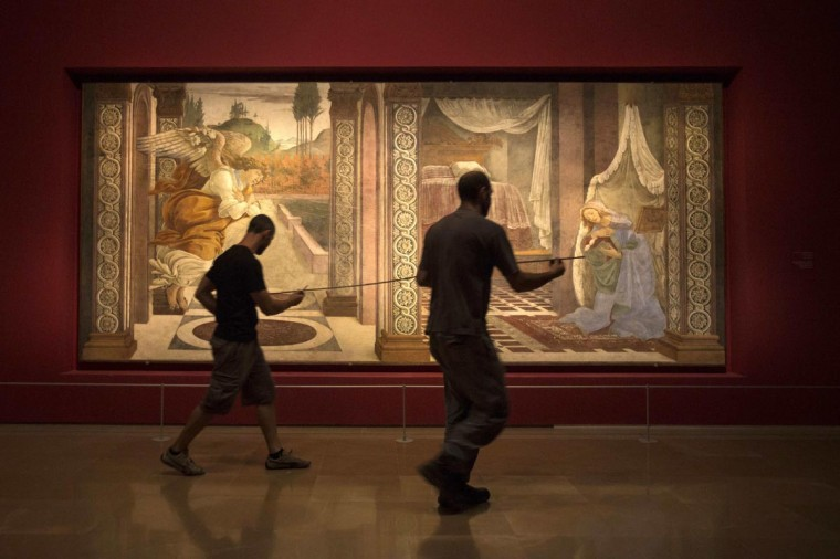 "Museum workers walk in front of a fresco by Italian renaissance painter Sandro Botticelli titled, ""The Annunciation of San Martino alla Scala"" at the Israel Museum in Jerusalem September 17, 2013. The fresco, on loan from the Uffizi Gallery in Florence, is the first Botticelli ever to be exhibited at the Israel Museum. (Baz Ratner/Reuters)"