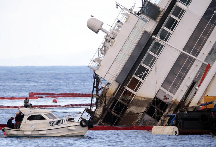 "Salvage crew workers are seen in front of the capsized cruise liner Costa Concordia after the start of the ""parbuckling"" operation outside Giglio harbor September 16, 2013. (Tony Gentile/Reuters)"
