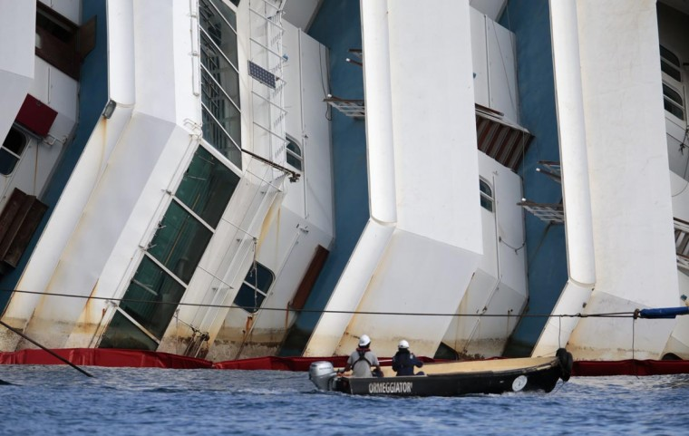 Salvage crew workers follow an operation to raise the capsized cruise liner Costa Concordia from a boat next to it, outside Giglio harbor September 16, 2013. (Tony Gentile/Reuters)
