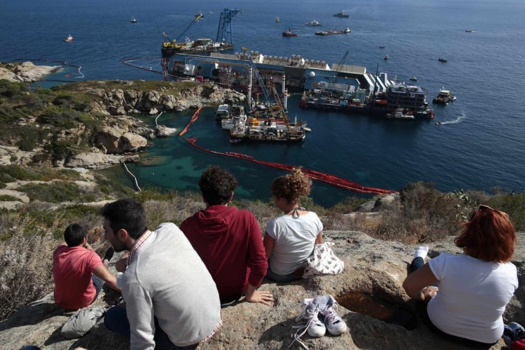 People look on as the capsized cruise liner Costa Concordia lies on its side next to Giglio Island September 16, 2013. (Tony Gentile/Reuters)