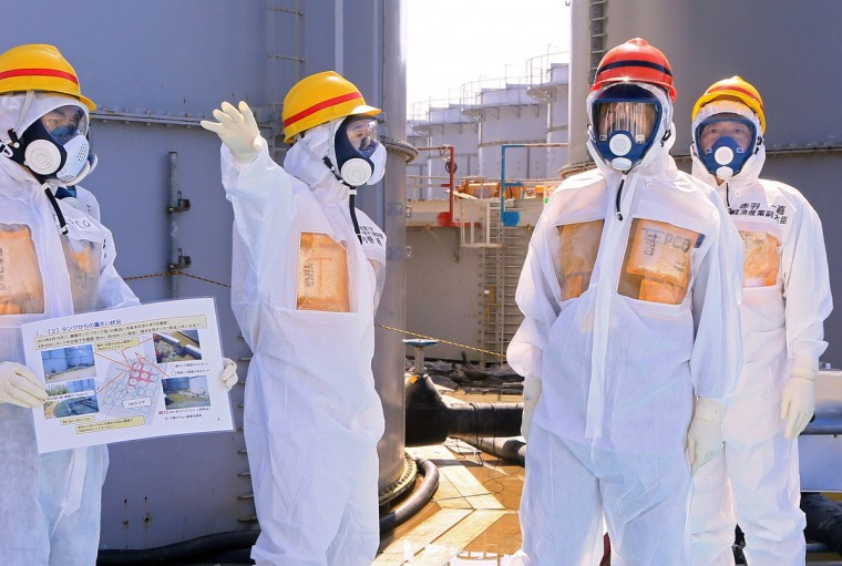 Japan's Prime Minister Shinzo Abe (2nd R), wearing protective suit and mask, is briefed about tanks containing radioactive water by Fukushima Daiichi nuclear power plant chief Akira Ono (2nd L), as they stand near a tank (C, with railings painted red and blue) which is being dismantled after leaking contaminated water, during his inspection tour to the Tokyo Electric Power Co. (TEPCO)'s tsunami-crippled Fukushima Daiichi nuclear power plant in Okuma, Fukushima Prefecture. (Pool photo/Reuters)