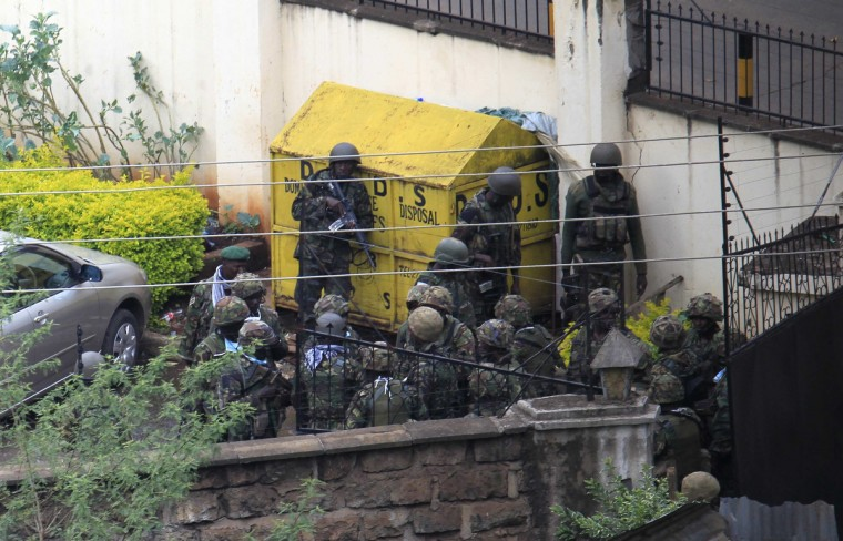 Kenya Defence Forces soldiers take cover behind a wall near the Westgate shopping centre after an exchange of gunfire inside the mall in Nairobi September 23, 2013. Thick smoke poured from the besieged Nairobi mall where Kenyan officials said their forces were closing in on Islamists holding hostages on Monday, three days after a raid by Somalia's al Shabaab killed at least 62 people. It remained unclear how many gunmen and hostages were still cornered in the Westgate shopping centre, two hours after a series of loud explosions and gunfire were followed by a plume of black smoke, that grew in volume from one part of the complex. (Noor Khamis/Reuters photo)