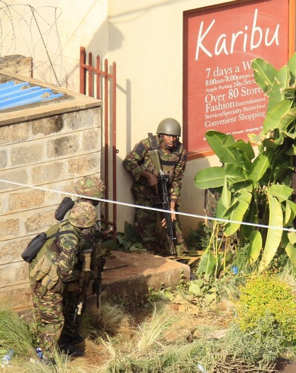 Kenya Defence Forces soldiers take cover behind walls near the Westgate shopping centre after an exchange of gunfire inside the mall in Nairobi September 23, 2013. Thick smoke poured from the besieged Nairobi mall where Kenyan officials said their forces were closing in on Islamists holding hostages on Monday, three days after a raid by Somalia's al Shabaab killed at least 62 people. It remained unclear how many gunmen and hostages were still cornered in the Westgate shopping centre, two hours after a series of loud explosions and gunfire were followed by a plume of black smoke, that grew in volume from one part of the complex. (Noor Khamis/Reuters photo)