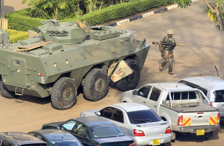 A Kenya Defence Forces soldier carrying a rocket-propelled grenade (RPG) walks past an armoured military vehicle in front of the Westgate shopping centre after an exchange of gunfire inside the mall in Nairobi September 23, 2013. Thick smoke poured from the besieged Nairobi mall where Kenyan officials said their forces were closing in on Islamists holding hostages on Monday, three days after a raid by Somalia's al Shabaab killed at least 62 people. It remained unclear how many gunmen and hostages were still cornered in the Westgate shopping centre, two hours after a series of loud explosions and gunfire were followed by a plume of black smoke, that grew in volume from one part of the complex. (Noor Khamis/Reuters photo)