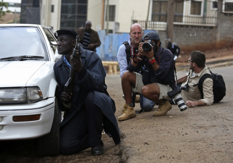 A policeman and photographers take cover after hearing gun shots near the Westgate shopping centre in Nairobi September 23, 2013. Thick smoke poured from the besieged Nairobi mall where Kenyan officials said their forces were closing in on Islamists holding hostages on Monday, three days after a raid by Somalia's al Shabaab killed at least 62 people. It remained unclear how many gunmen and hostages were still cornered in the Westgate shopping centre, two hours after a series of loud explosions and gunfire were followed by a plume of black smoke, that grew in volume from one part of the complex. (Karel Prinsloo/Reuters photo)