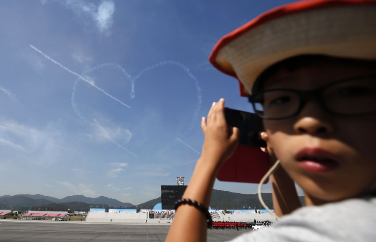 "A boy takes photographs during a display by the South Korean air force aerobatic team ""Black Eagles"" at a rehearsal for the upcoming anniversary of the Armed Forces Day at a military airport in Seongnam, south of Seoul. (REUTERS/Kim Hong-Ji)"