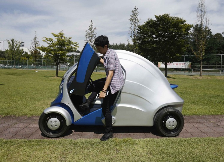"A researcher gets out of Armadillo-T, a foldable electric vehicle, at the Korea Advanced Institute of Science and Technology (KAIST) in Daejeon, south of Seoul. With a click on a smartphone, the experimental ""Armadillo-T"" electric car made in South Korea will park itself and fold nearly in half, freeing up space in crowded cities. The quirky two-seater, named after the animal whose shell it resembles, may never see production but it is part of a trend of developing environmentally friendly vehicles for urban spaces. (Kim Hong-Ji/Reuters)"