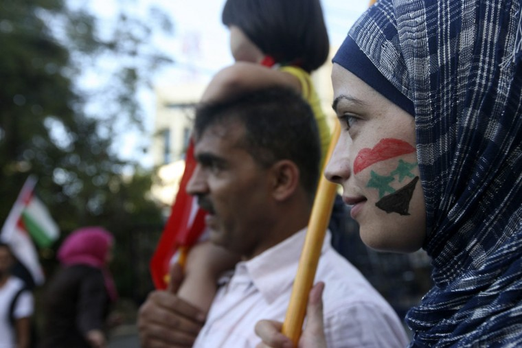 "An activist with a Syrian flag drawn on her face attends a sit-in near the U.S. embassy in Awkar, north of Beirut, against potential U.S. strikes on Syria September 7, 2013. U.S. officials ordered non-emergency personnel and their family members out of Lebanon on Friday ""due to threats,"" the U.S. embassy in Beirut said in a statement. (Hasan Shaaban/Reuters)"