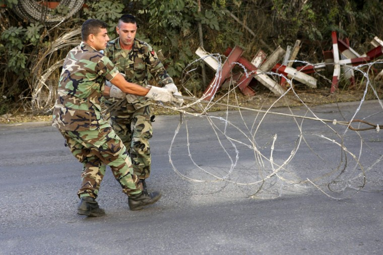 "Lebanese army soldiers install barbed wire to close a road leading to the U.S. embassy in Awkar, north of Beirut, before a protest against potential U.S. strikes on Syria, September 7, 2013. U.S. officials ordered non-emergency personnel and their family members out of Lebanon on Friday ""due to threats,"" the U.S. embassy in Beirut said in a statement. (Hasan Shaaban/Reuters)"