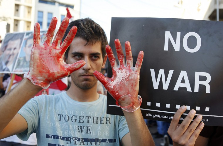 "An activist shows his hands while wearing gloves covered in fake blood during a sit-in near the U.S. embassy in Awkar, Lebanon, September 6, 2013. The sit-in was against potential U.S. strikes on Syria. U.S. officials ordered non-emergency personnel and their family members out of Lebanon on Friday ""due to threats,"" the U.S. embassy in Beirut said in statement. (/Mohamed Azakir/Reuters)"