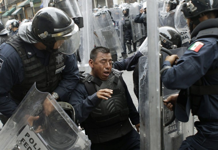 Riot policemen attend to a colleague who was injured during the protests in downtown Mexico City. (Henry Romero / Reuters)