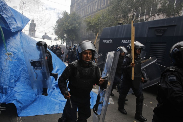 Riot policemen charge toward protesters in downtown Mexico City. (Tomas Bravo / Reuters)