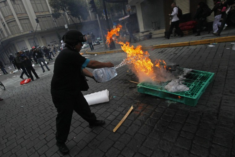 A protesters puts out a fire as striking members of the teachers' union CNTE are evicted from Zocalo Square in downtown Mexico City. (Edgard Garrido / Reuters)