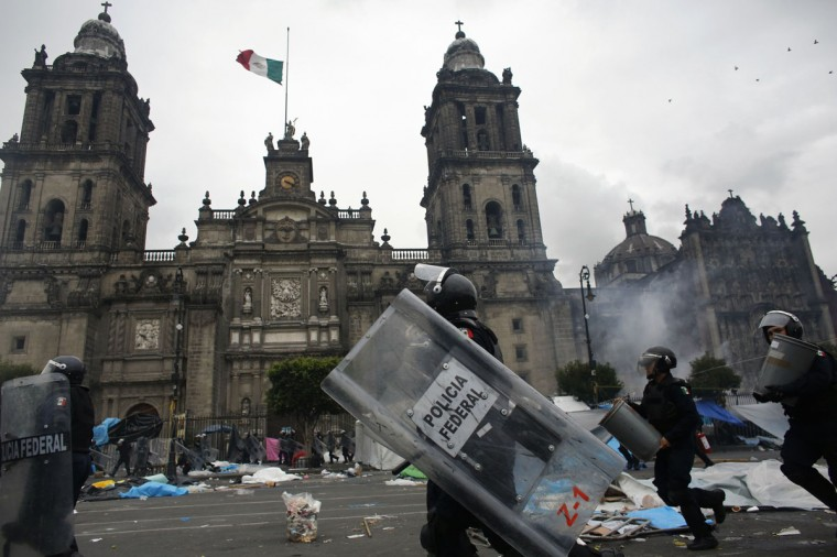 Riot policemen charge past the cathedral during protests in Mexico City. (Tomas Bravo / Reuters)