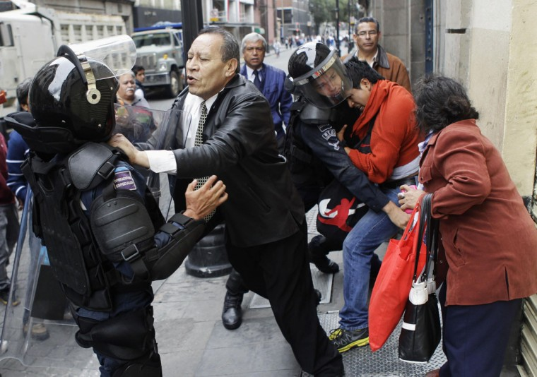 People confront riot policemen who are trying to arrest a protester in downtown Mexico City. (Henry Romero / Reuters)